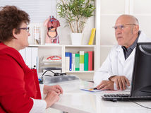Portrait: older doctor with experience talking with senior woman Stock Photo