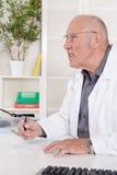 Portrait of an older male doctor sitting at desk. Stock Image