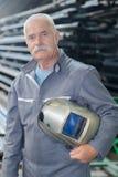 Portrait older male steel worker welding with protective mask. Portrait of older male steel worker welding with protective mask Royalty Free Stock Photo