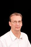 Portrait of older man on black in white shirt. Portrait of older man with glasses in white dress  shirt against a black background Stock Images