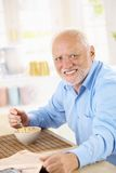 Portrait of older man eating cereal. Portrait of healthy older man eating cereal for breakfast, looking at camera, smiling royalty free stock photos