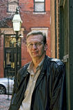 Portrait of older man leaning on wall. Portrait of older man leaning against brick outside wearing glasses and a leather jacket in beacon hill boston Royalty Free Stock Images