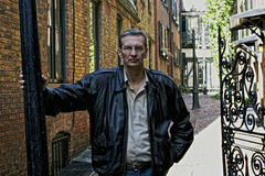 Portrait of older man outside at gate. Leaning on pole wearing glasses and a leather jacket in beacon hill boston Stock Photography