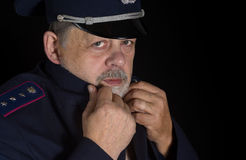 Portrait of older man in police uniform. In low key Royalty Free Stock Photography