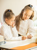 Portrait of older sister helping with homework to younger one Royalty Free Stock Photography