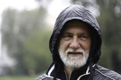 Portrait of an older white bearded man wearing a black hoodie on a rainy day with a blurry background Royalty Free Stock Image
