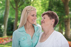 Portrait: older woman with her granddaughter or daughter in the. Portrait of a older women with her granddaughter or daughter in the garden Royalty Free Stock Photos