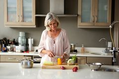 Older woman preparing food for a meal in kitchen Stock Photos