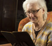 Portrait of an older woman reading book Stock Image