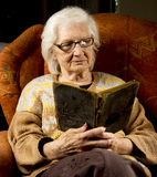Portrait of an older woman reading book Stock Photos