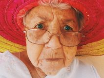 Portrait of older woman in red hat Stock Images