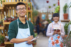 Portrait of One Happy Young Male Florist in Shop. One Young Happy Asian Male Florist Working in Shop Royalty Free Stock Photo
