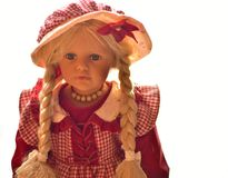 Portrait of One porcelain doll. With white background and a lot of copy space. Not so new. Old-looking doll. In red clothes Royalty Free Stock Photos