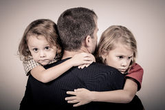 Portrait of one sad children hugging her father. Near a wall Royalty Free Stock Photography