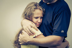 Portrait of one sad daughter hugging his father. At the day time Stock Photo