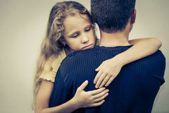 Portrait of one sad daughter hugging his father Stock Photos
