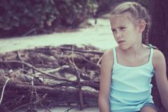 Portrait of one sad little girl. Child sitting on the beach at the day time. Concept of sorrow Stock Image