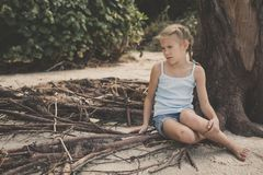 Portrait of one sad little girl. Child sitting on the beach at the day time. Concept of sorrow stock photos