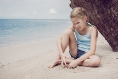 Portrait of one sad little girl. Child sitting on the beach at the day time. Concept of sorrow royalty free stock photo