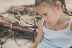 Portrait of one sad little girl. Child sitting on the beach at the day time. Concept of sorrow royalty free stock photography