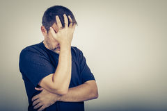 Portrait one sad man standing near a wall. And covers his face Stock Photo