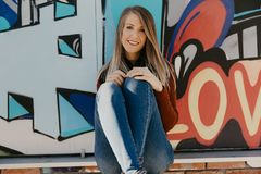Portrait of Pretty Cute Young Blond Adult Woman Outside in Chilly Season Downtown Urban Street Art District Sitting in Front of Vi royalty free stock images