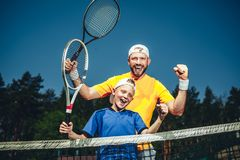 Satisfied man and boy playing tennis stock photography