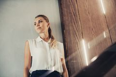 Serene lady thinking and leaning against wall royalty free stock images