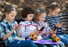 Portrait of ordinary kids playing with phones. Outdoor portrait of ordinary kids playing with phones Royalty Free Stock Photo