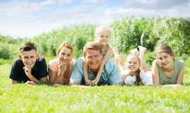 Portrait of ordinary large family lying on green lawn outdoors Royalty Free Stock Photos