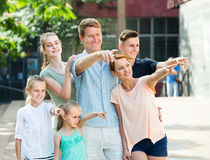 Portrait of ordinary large family standing pointing with finger Royalty Free Stock Photography