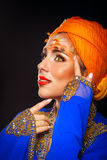 Portrait of oriental beauty in a turban and face art. Royalty Free Stock Image