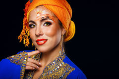 Portrait of oriental beauty in a turban and face art. Stock Photography