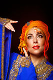 Portrait of oriental beauty in a turban and face art. Royalty Free Stock Photo