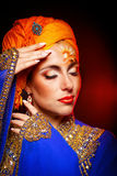 Portrait of oriental beauty in a turban and face art. Royalty Free Stock Photos
