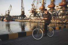Young man with brown hair standing with bicycle and dreamily looking in his mobile phone.Thoughtful boy in down jacket. Portrait of oung man with brown hair Stock Photography