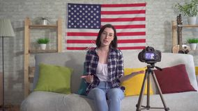 Portrait oung woman blogger in shirt on American flag background recording video. Portrait young woman blogger in shirt and glasses on American flag background stock video footage