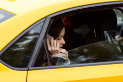 Portrait out window car of pensive woman talking on cellphone Royalty Free Stock Images