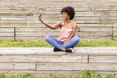 portrait outdoors of a beautiful young afro american woman at sunset using mobile phone. wood background. Lifestyle.Sitting on royalty free stock photography