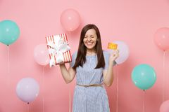Portrait of overjoyed woman with closed eyes in blue dress hold credit card and red box with gift present on pink. Background with colorful air balloon royalty free stock image