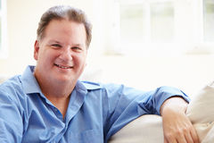Portrait Of Overweight Man Sitting On Sofa Stock Photos