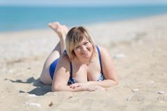 Portrait of overweight woman in one-piece swimsuit at sea. Overweight woman in blue one-piece swimsuit at the sea. Fat girl in blue swimwear lying on sand and Stock Photography