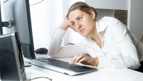 Portrait of overworked young businesswoman looking at computer screen. Portrait of overworked businesswoman looking at computer screen Royalty Free Stock Image