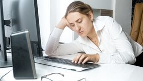 b1153ec78 Portrait of overworked young businesswoman working with closed eyes royalty  free stock photo