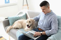Portrait of owner with his friendly dog using laptop. At home stock images