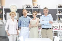 Portrait of owners and staff standing against counter in restaurant royalty free stock image
