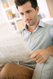 Portrait oy young man sitting in sofa with newspaper in hands Stock Photo