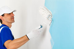 Portrait of painter painting a wall Stock Images