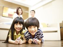 Portrait of a pair of asian brother and sister. Asian brother and sister lying on front on floor with parents in the background Royalty Free Stock Image