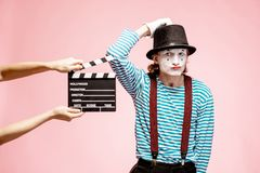 Portrait of a pantomime with cinematography clapperboard. Portrait of an actor as a pantomime with cinematography clapperboard on the pink background royalty free stock photography